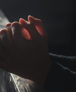 Hands together resting on church pew row in front of the person