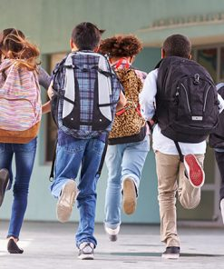 Primary school kids running with their backpacks towards the school doors