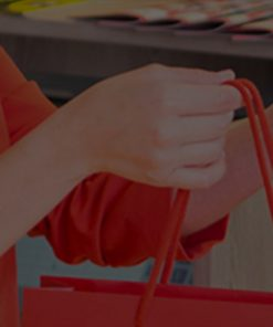 Woman In Red Shirt Holding A Red Shopping Bag